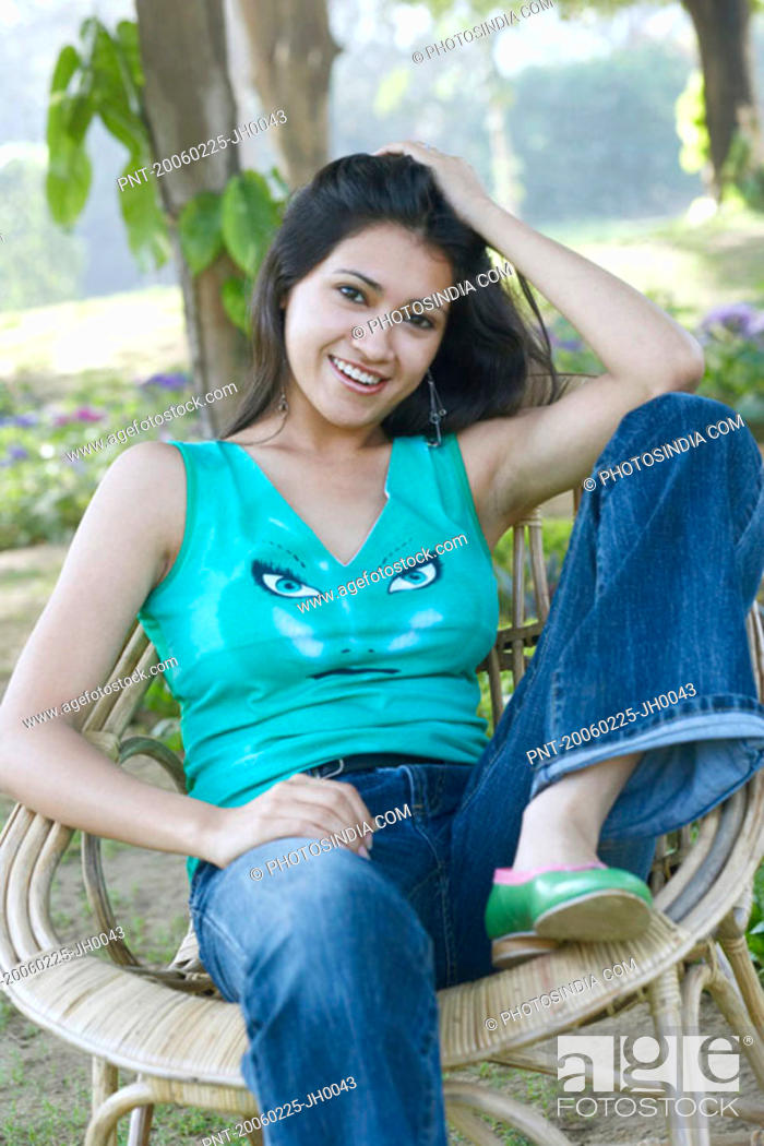 Stock Photo: Portrait of a young woman sitting in an armchair and smiling.