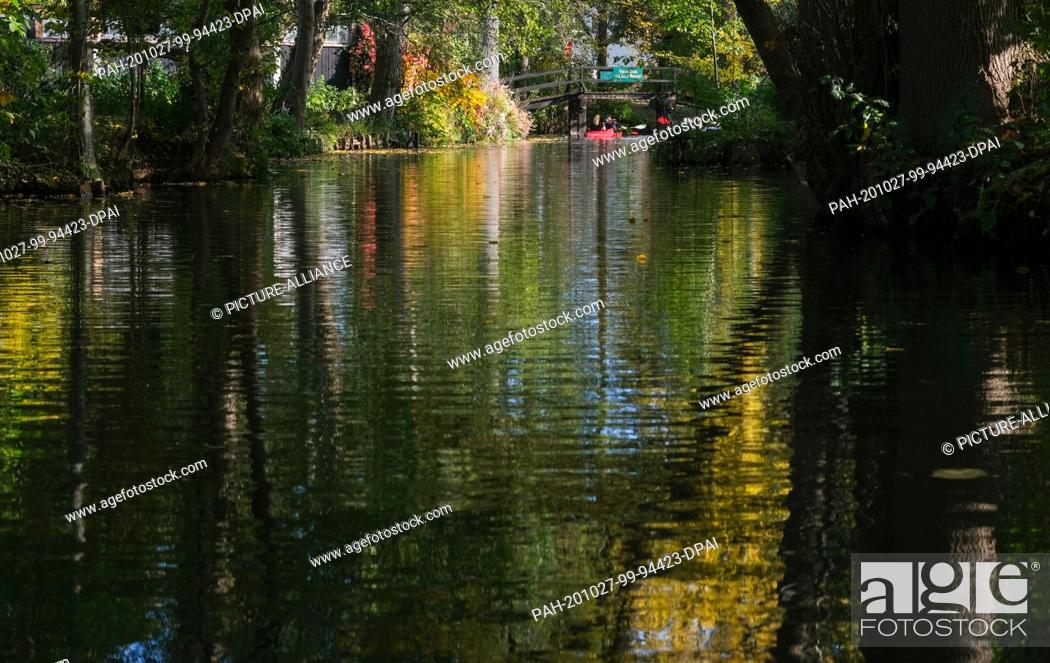 Stock Photo: 25 October 2020, Brandenburg, Schlepzig: Canoes are on a river in the Spreewald. The leaves of the trees along the water have turned an autumnal colour.