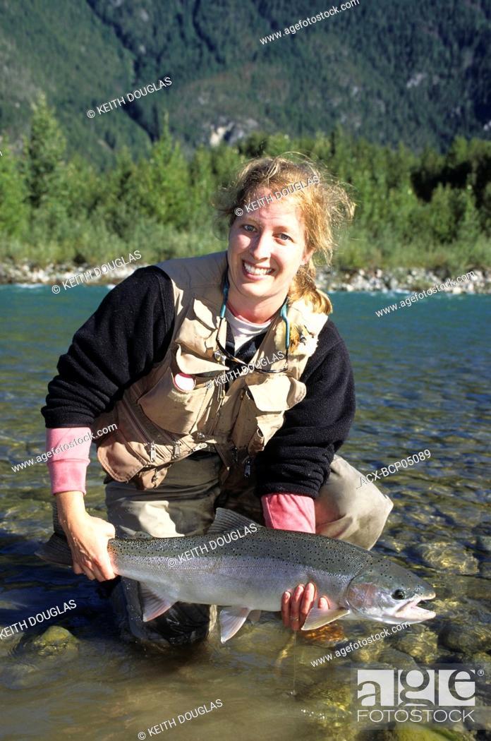 Photo de stock: Lady angler holding steelhead, Dean river, British Columbia, Canada.