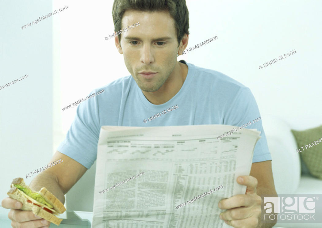Stock Photo: Young man reading newspaper and eating sandwich.