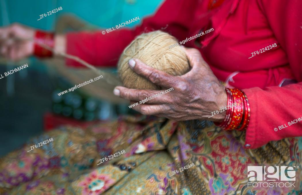 Stock Photo: Nepal. Nepali weaving woman, posing and weaving threads for carpets. Nayapati, Eastern Kathmandu. 43.