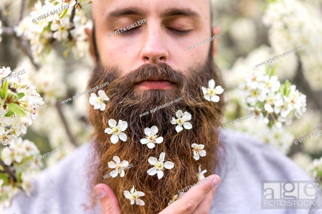 Stock Photo: Portrait of hipster with white tree blossoms in his beard.