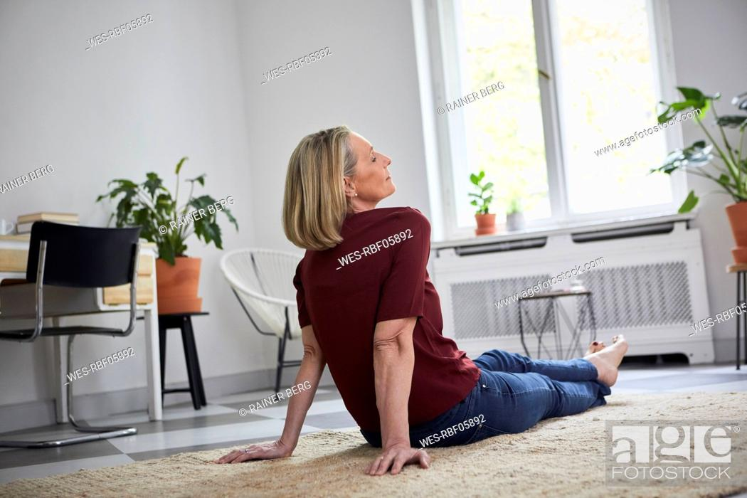 Stock Photo: Relaxed mature woman sitting on the floor at home.
