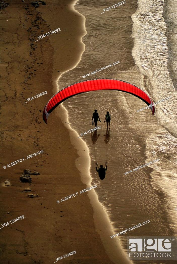 Stock Photo: Paragliding and couples strolling on the beach Torimbia, Llanes, Asturias.