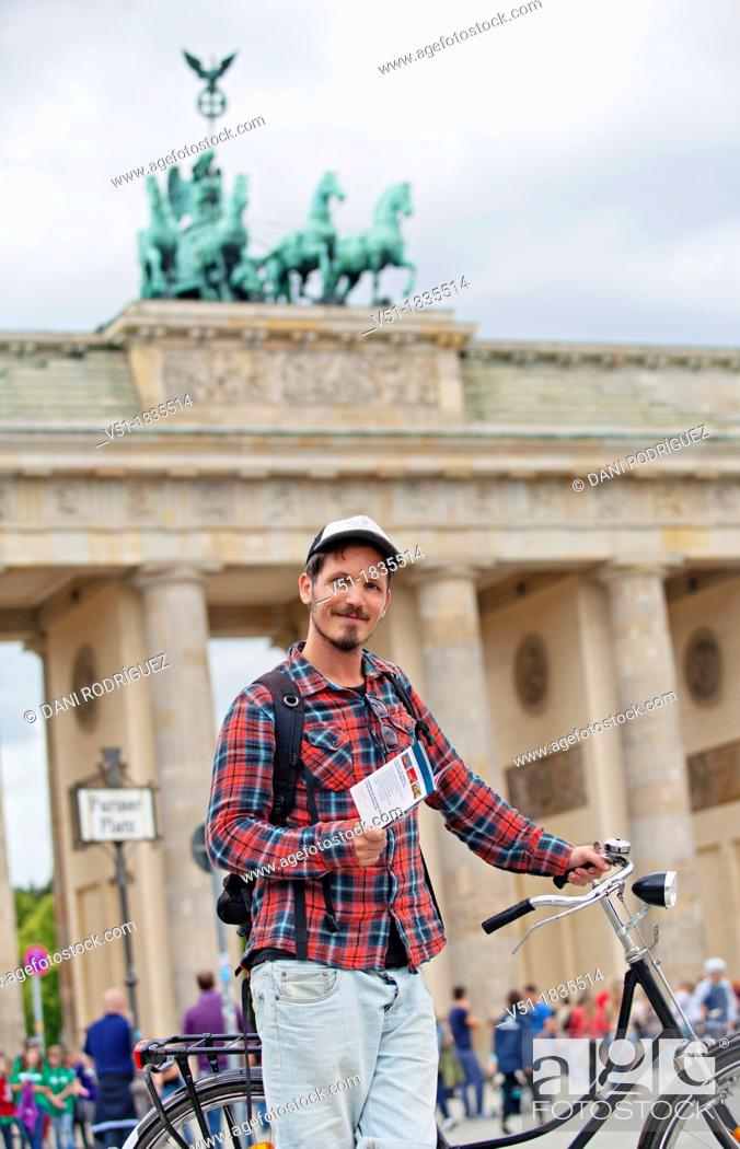 Photo de stock: Tourist with bike and guide book in Brandenburg Gate, Berlin, Germany.