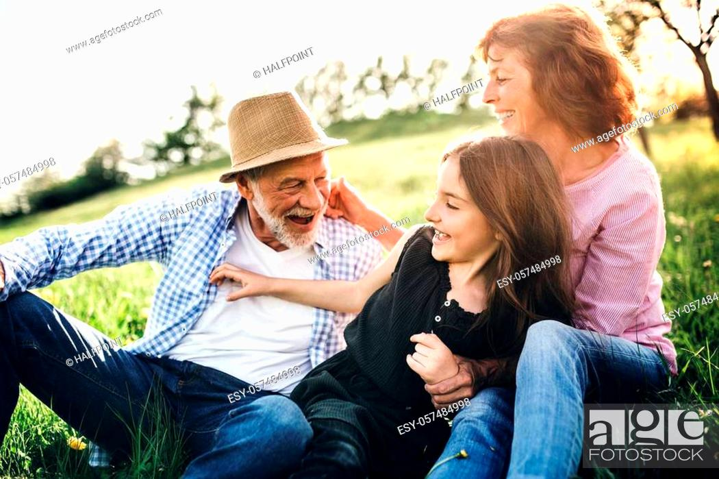 Stock Photo: Senior couple with granddaughter outside in spring nature, relaxing on the grass and having fun.