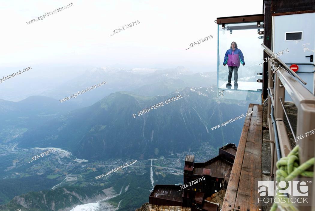 Stock Photo: Woman in a crystal box on the void, Pas dans le Vide - step into the void - at 3842 m, Aiguille du Midi, Chamonix-Mont-Blanc, Haute-Savoie, France, Europe.