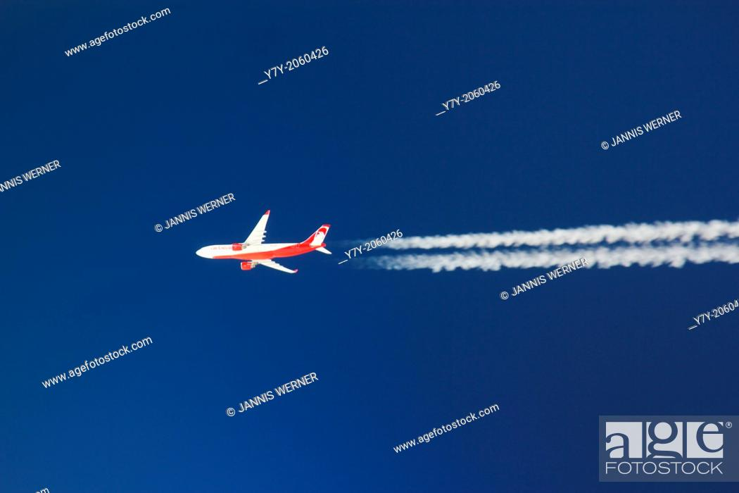 Stock Photo: Air Berlin airplane brightly lit in a clear deep blue sky.