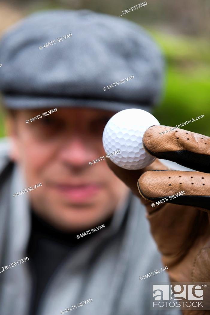 Stock Photo: Golfer with flat cap and a glove holding up a golf ball in Ascona, Switzerland.