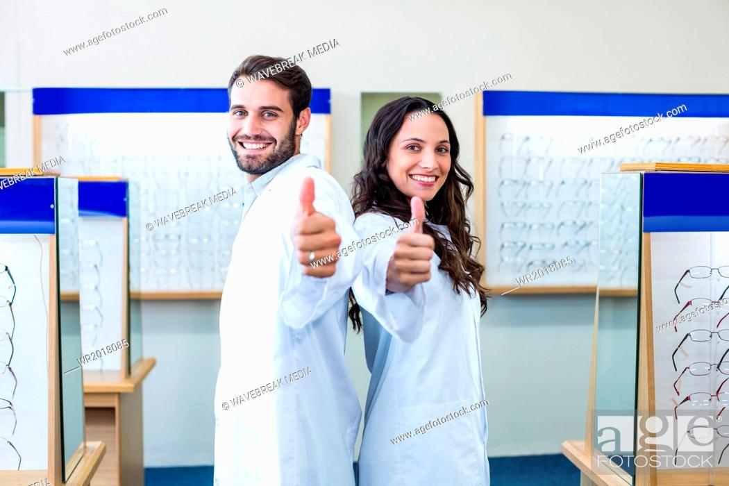 Stock Photo: Two happy optician back to back with thumbs up.