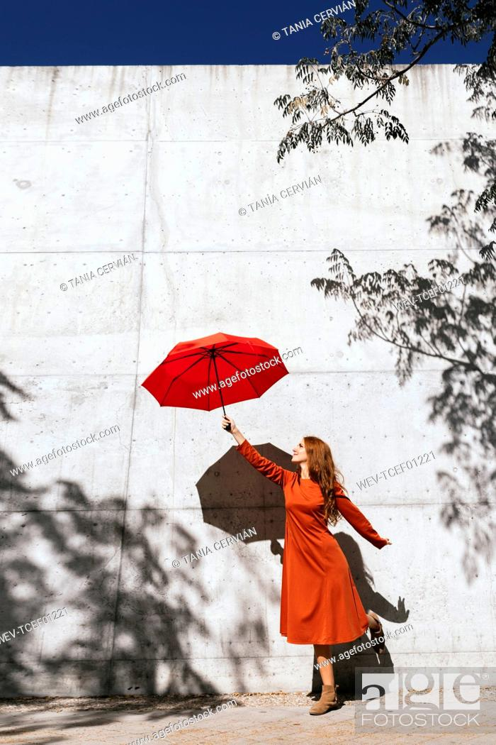 Stock Photo: Young woman in red dress holding flying umbrella while standing against tree shadow wall.