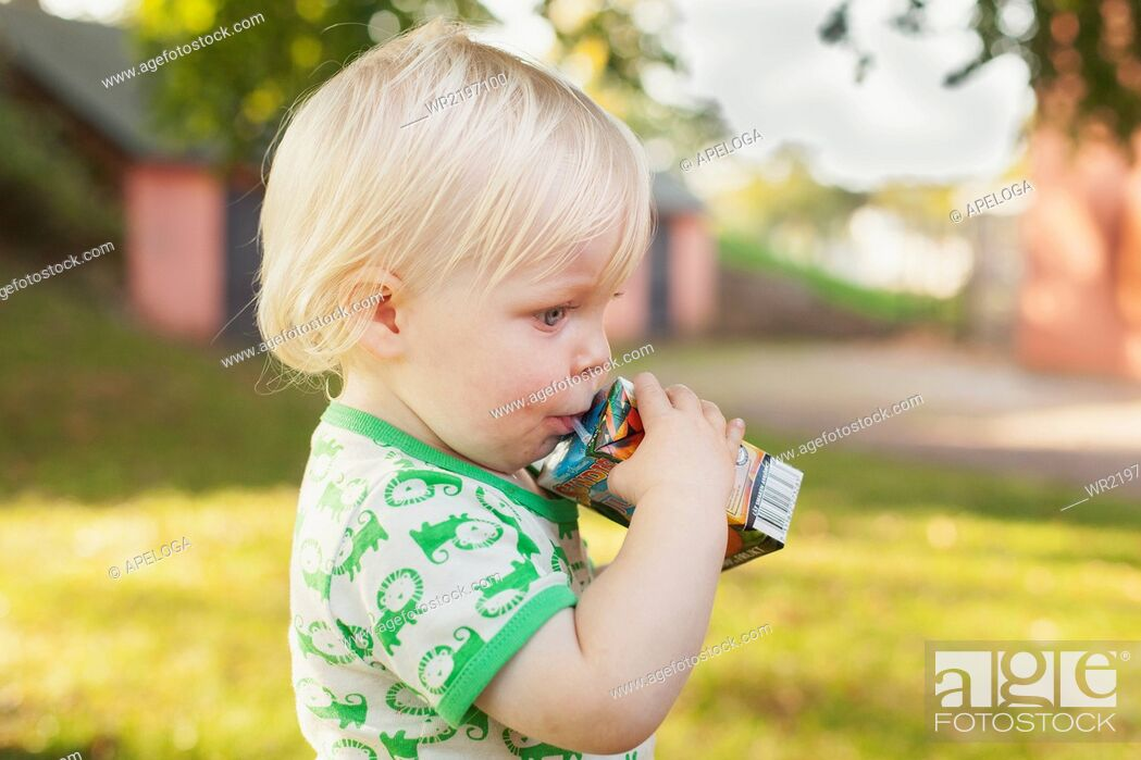 Imagen: Side view of cute baby boy drinking from juice box at park.