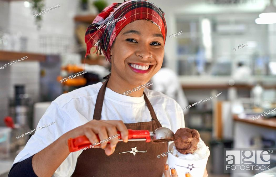 Stock Photo: Young woman working in ice cream parlour, filling cup with icecream.