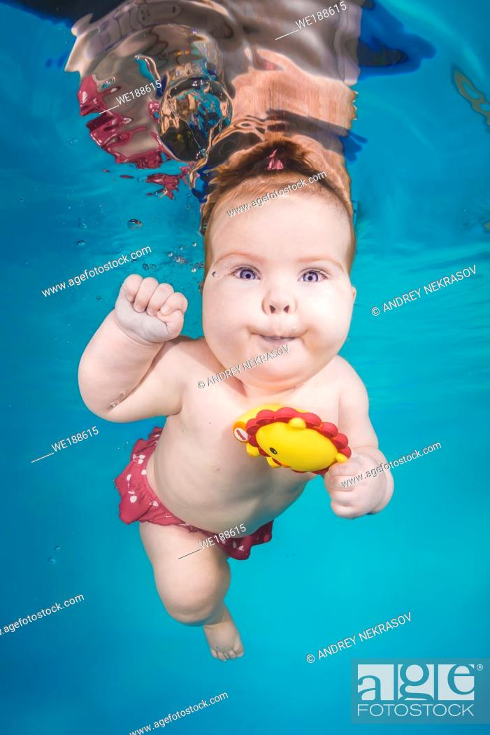Stock Photo: Cute chubby little girl plays with toy underwater in a swimming pool.