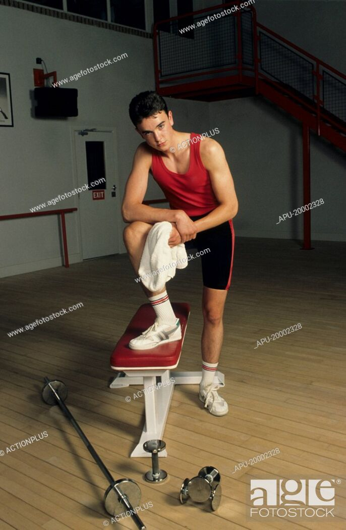 Stock Photo: Young man in a gym with a bench and free weights.