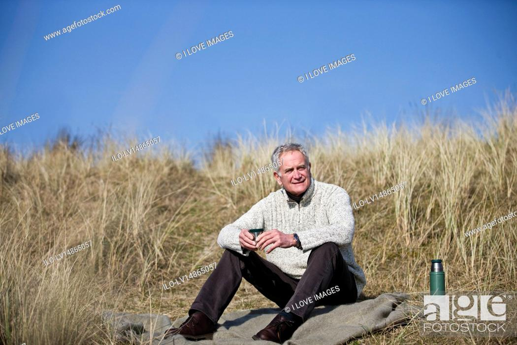 Stock Photo: A senior man sitting amongst the sand dunes, having a hot drink.