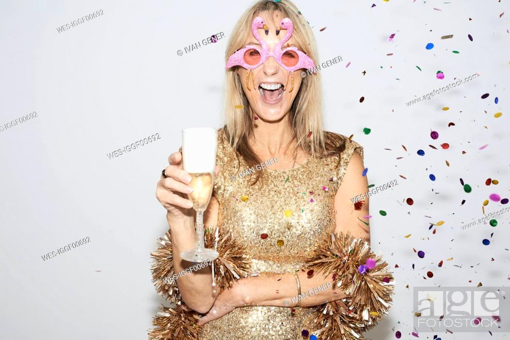 Imagen: Senior woman wearing golden dress and flmingo shaped glasses, celebtraing New Year's Eve.