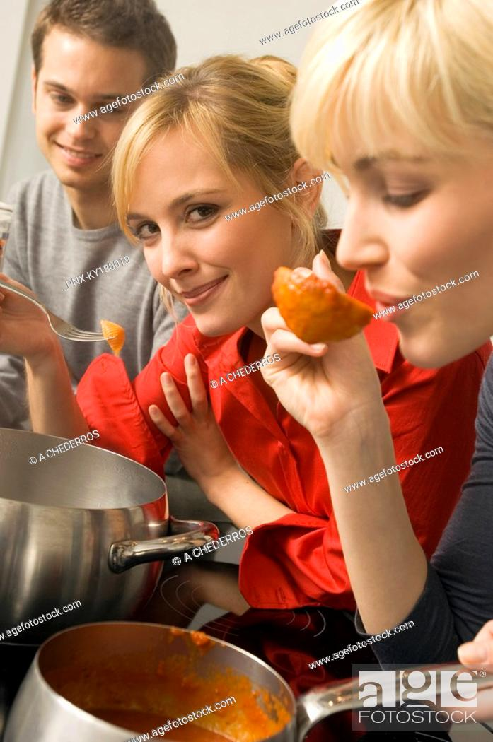 Stock Photo: Young woman tasting tomato sauce with a ladle with a young man and a young woman beside her in the kitchen.