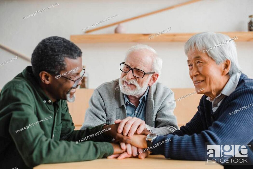 Imagen: group of multiethnic senior friends making team gesture and smiling.
