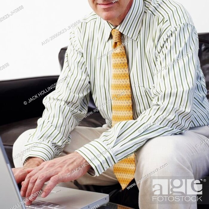 Stock Photo: Portrait of a businessman sitting on a couch and using a laptop.