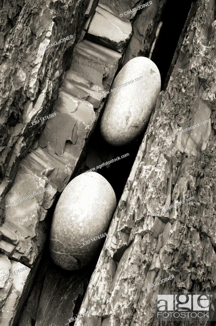 Stock Photo: Two pebbles trapped in a crack in the sedimentary rock of Cornborough Cliff on the North Devon Coast, England, United Kingdom.