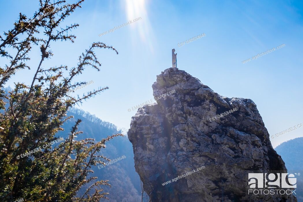 Stock Photo: Italy, Lombardy, Varese, statue of the most holy Virgin Mary over a rock, bathed in rays of sun from the sky.