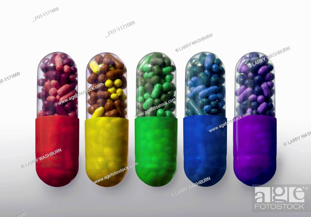 Stock Photo: A row of vibrantly variously colored capsule pills, close-up.