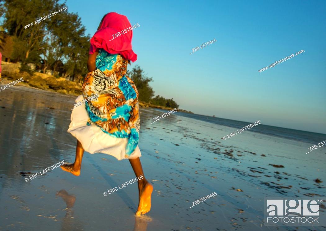Stock Photo: Tanzania, Zanzibar, Kizimkazi, young muslim girl in school uniform running on beach.