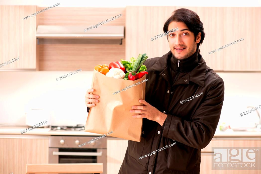 Stock Photo: Young handsome man with vegetables in the kitchen.