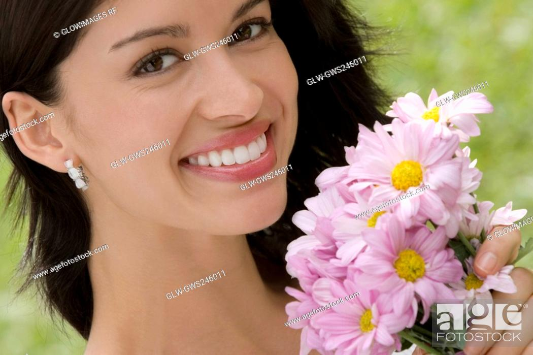 Stock Photo: Portrait of a young woman holding a bouquet of flowers and smiling.