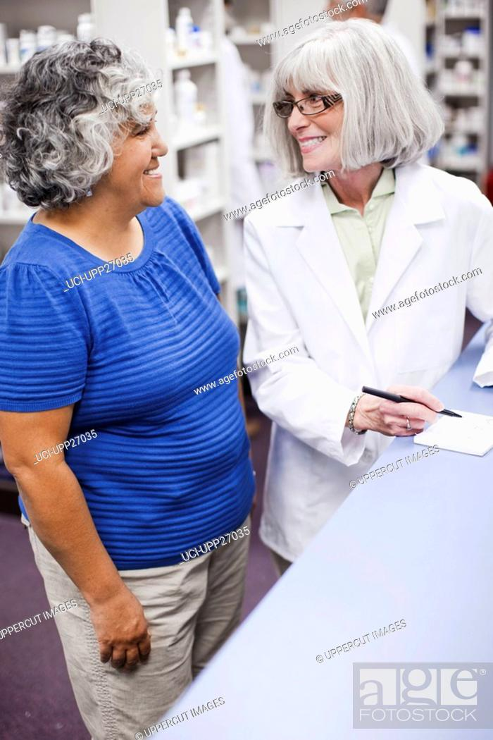 Stock Photo: Pharmacist assisting customer.