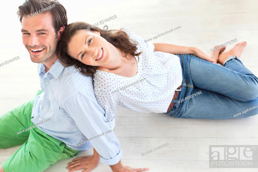 Stock Photo: Portrait of smiling couple sitting on floor.