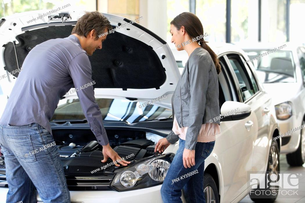 Stock Photo: Couple looking at car engine in showroom.