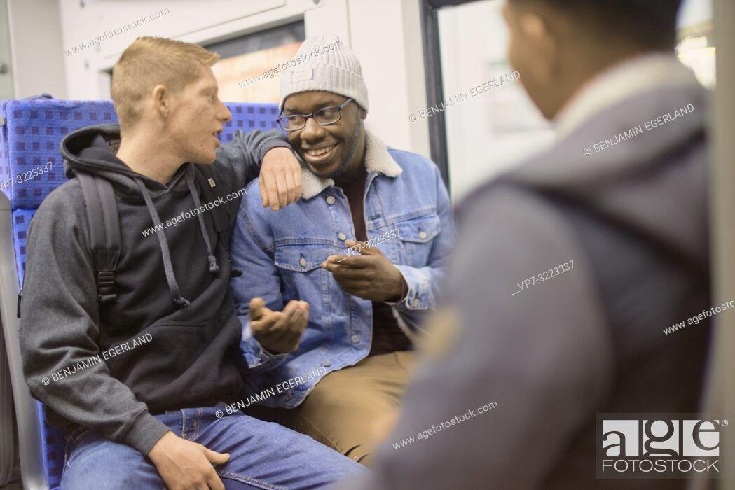 Imagen: young men talking in public transport, in Munich, Germany.