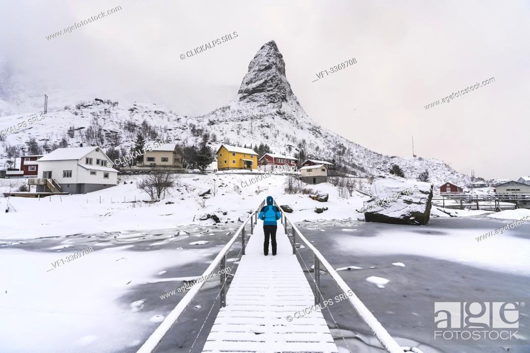 Stock Photo: Woman standing on a wooden bridge under the snow, looking towards Hammarskaftet peak. Reine, Nordland county, Northern Norway, Norway.