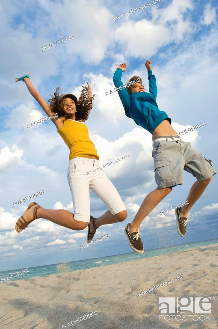 Stock Photo: Teenage boy with a girl jumping on the beach.