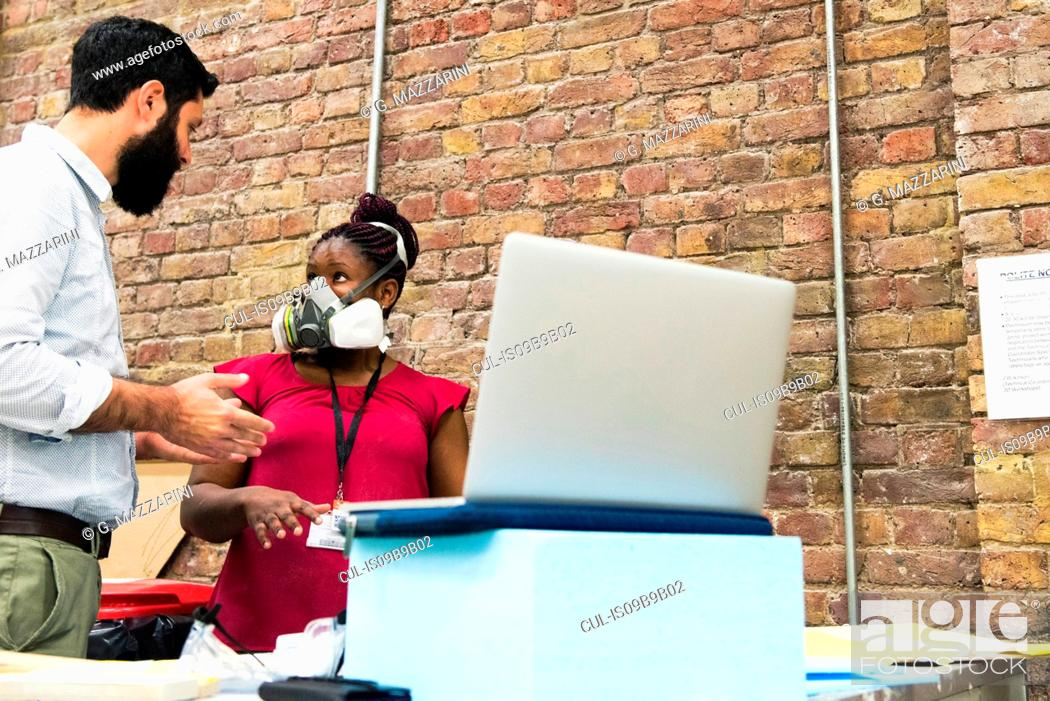 Imagen: Tutor in art college chatting to student wearing protective mask.