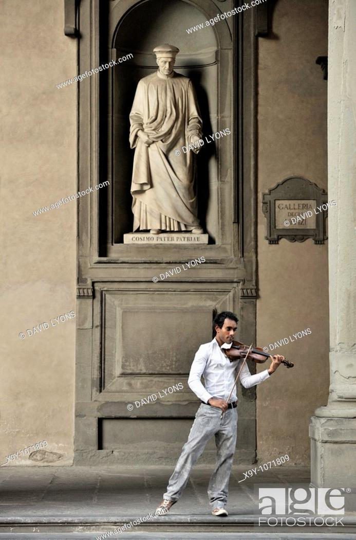Photo de stock: Florence, Italy  Street musician plays classical violin under statue of city father Cosimo de Medici  Outside the Uffizi Gallery.