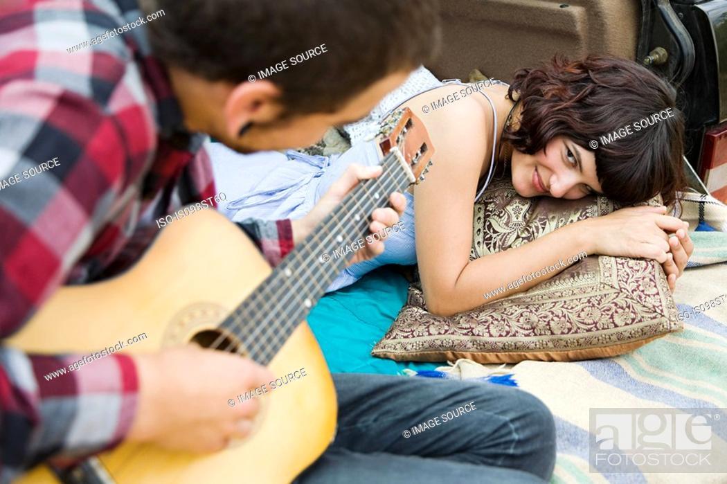 Stock Photo: Young man playing guitar to girlfriend.