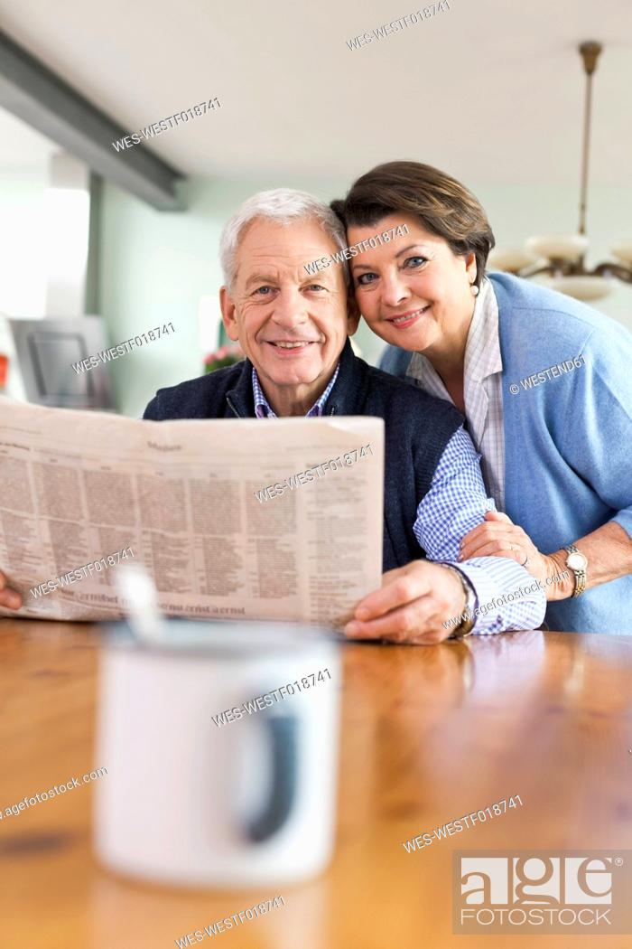 Stock Photo: Germany, Leipzig, Senior man and woman with newspaper, smiling, portrait.