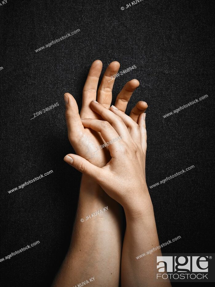 Stock Photo: Man and woman, hands connecting together, dark canvas background.