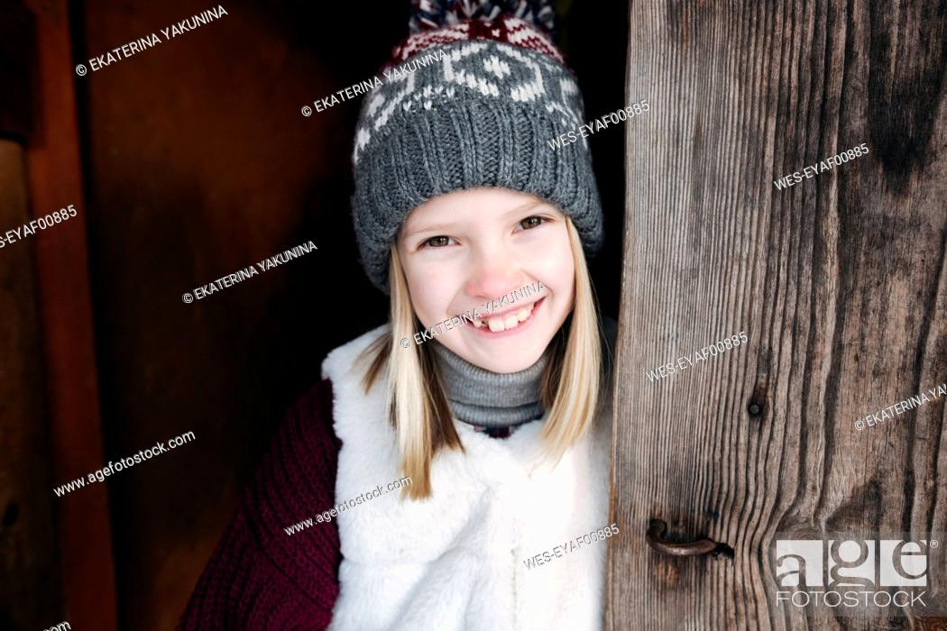 Stock Photo: Portrait of happy girl wearing woolly hat at wooden wall.