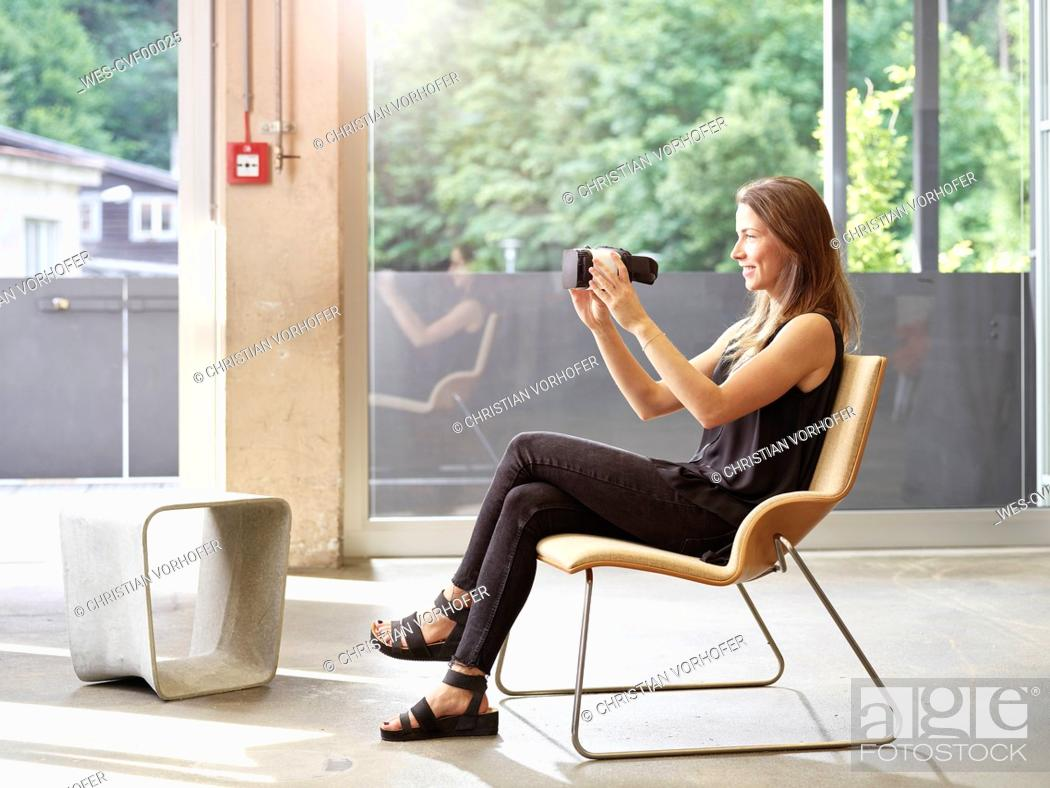 Stock Photo: Woman holding VR glasses sitting on chair.