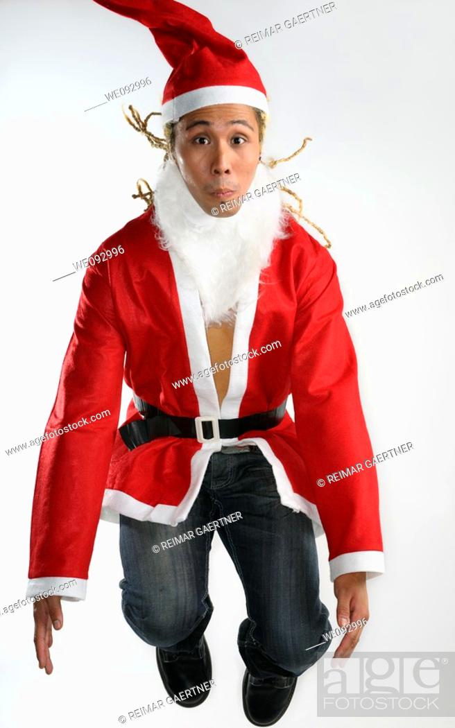 Stock Photo: Man with dreadlocks dressed as Santa Claus jumping in the air.