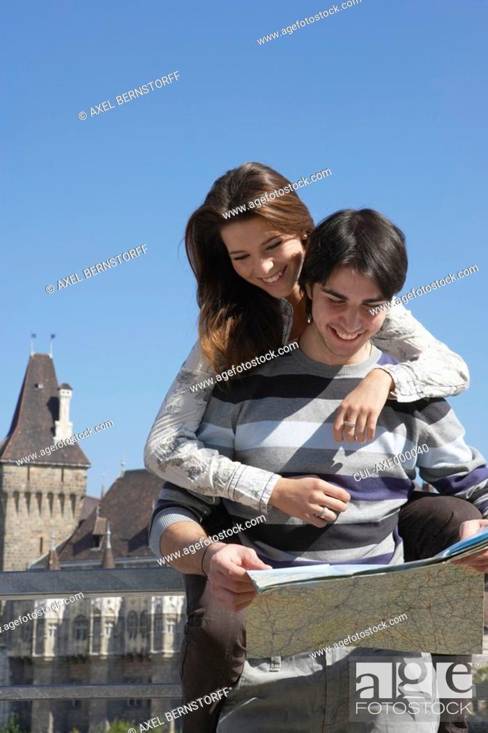 Stock Photo: Couple looking at a map outdoors smiling.
