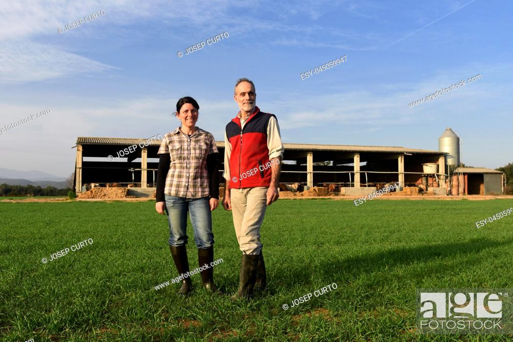 Photo de stock: Portrait of a couple farmer in the countryside with a farm at sunset background.