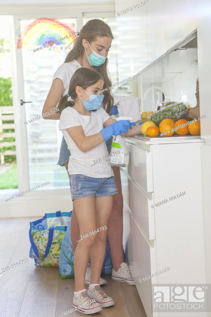 Stock Photo: girls wearing masks and gloves cleaning groceries.