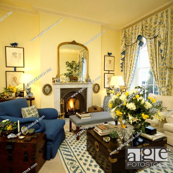 Traditional yellow living room with blue armchair and ...