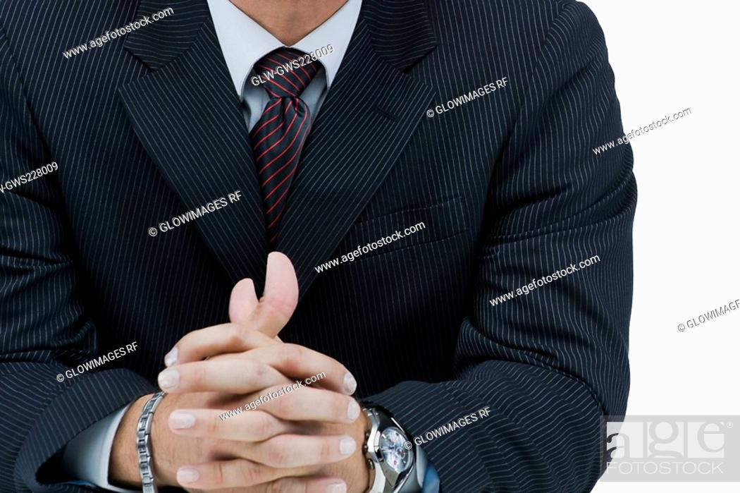 Stock Photo: Mid section view of a businessman with his hands clasped.