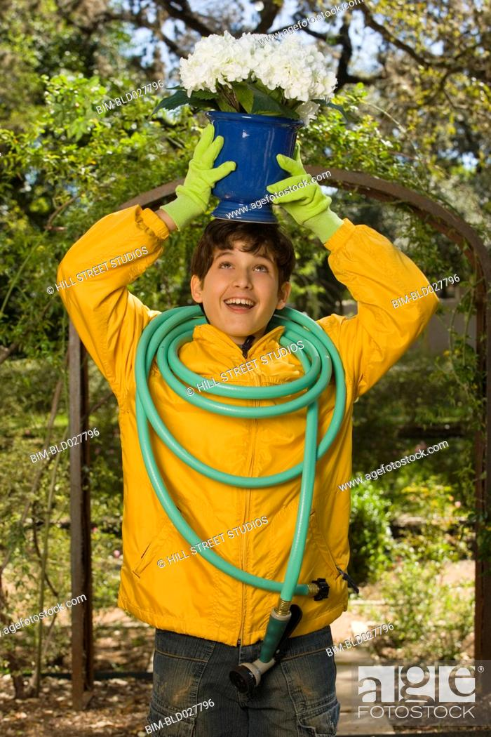 Stock Photo: Boy holding potted plant on head and hose on shoulders.